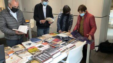 La responsable de la Biblioteca Josep Benet consultant els llibres donats amb els representants borgencs